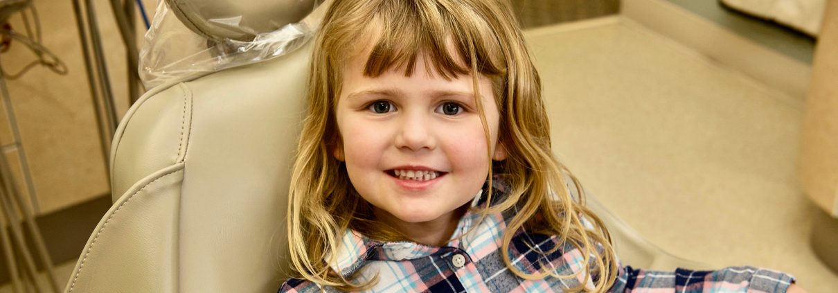 young blonde girl smiles at stow pediatric dentist visit at Munroe Falls Family Dentistry on Darrow Road on the border of Stow and Munroe Falls, Ohio