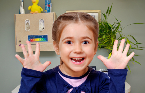 girl smiles shows 10 fingers to count ten ways to prevent cavities in your child