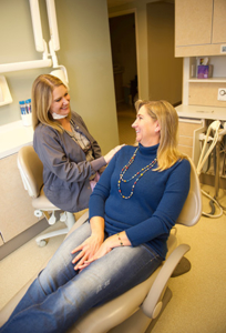 Family dentist near Cuyahoga Falls, Ohio talks with woman about how vaping causes tooth decay