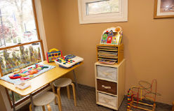 table shows kid-sized chairs with puzzles and building toys next to toy bin inside child play and waiting area at Munroe Falls Family Dentistry on the border of Stow Ohio on Darrow Road