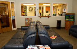 waiting area in front entrance of Munroe Falls Family Dentistry near Stow Ohio features comfortable blue leather couches and tropical fish tank